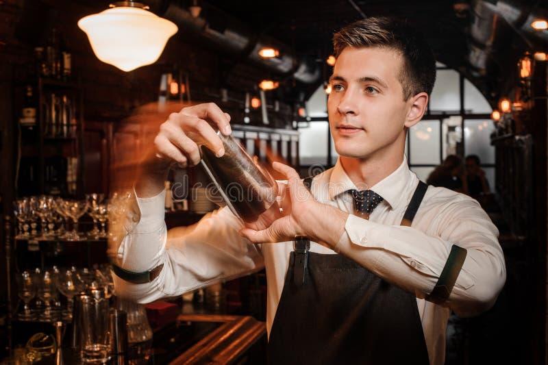 震动一新和鲜美夏天cockt的年轻和英俊的男服务员 免版税库存照片