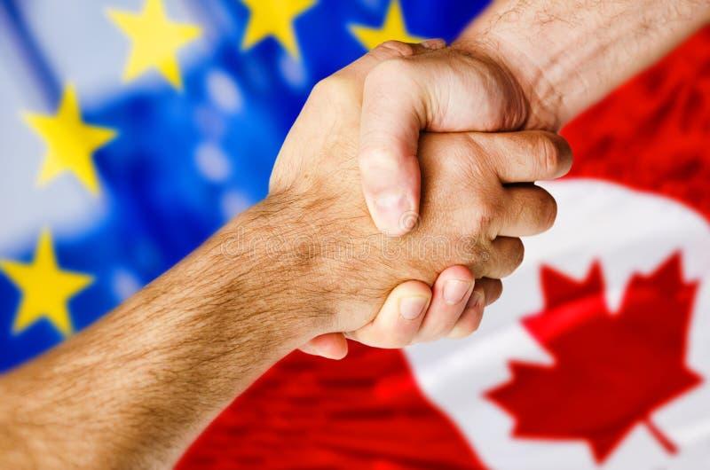 震动在加拿大和欧洲旗子的手 免版税库存图片