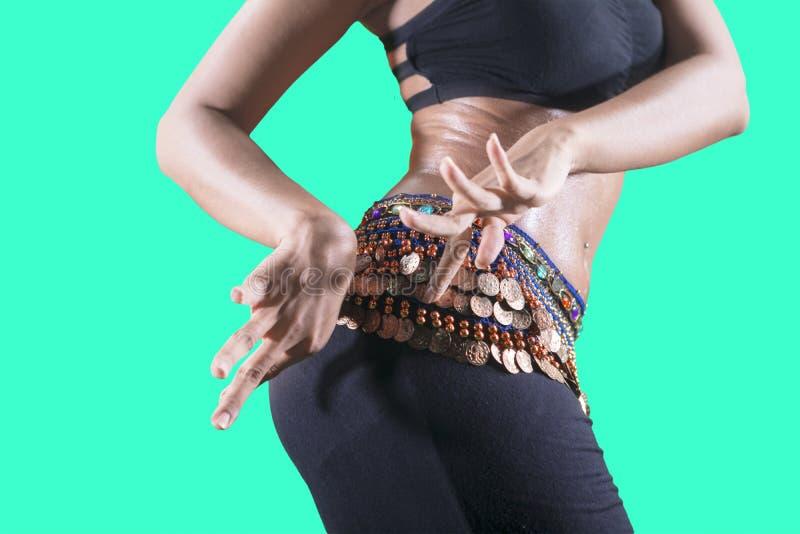 震动她的在演播室的未知的肚皮舞表演者臀部 图库摄影