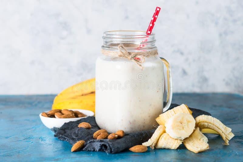 震动或圆滑的人从杏仁牛奶、香蕉和椰子 库存照片
