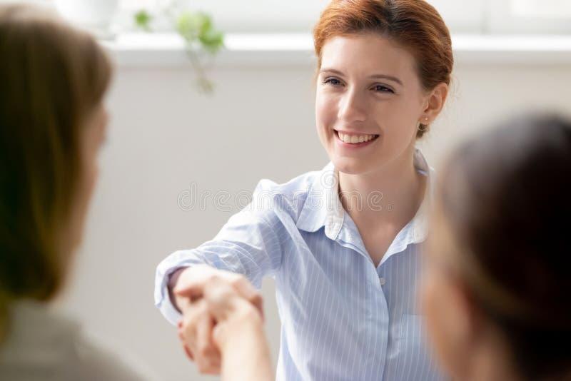 震动手客户,新的同事,空位候选人的微笑的女实业家问候 免版税库存照片