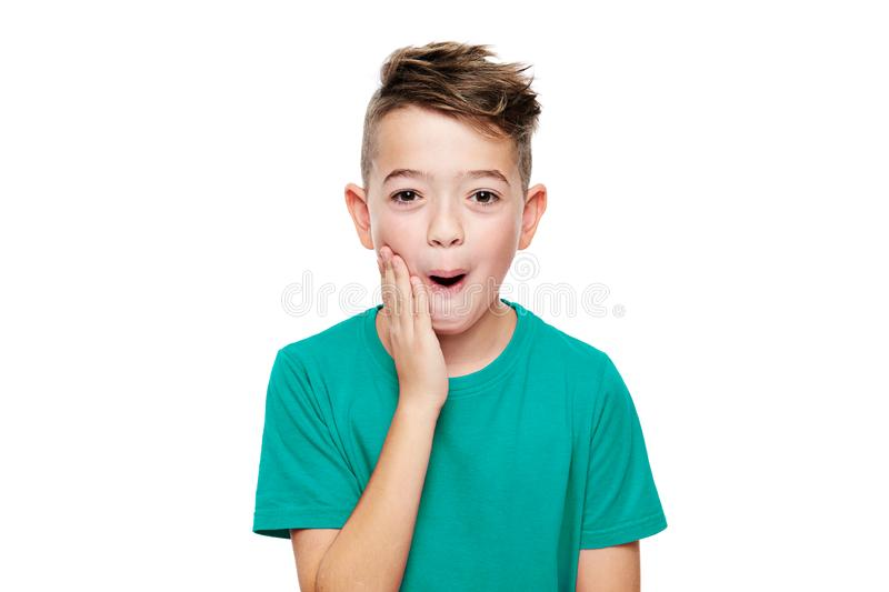 震动的可爱的年轻男孩,被隔绝在白色背景 怀疑地看照相机的震惊孩子 震动,触目惊心 图库摄影