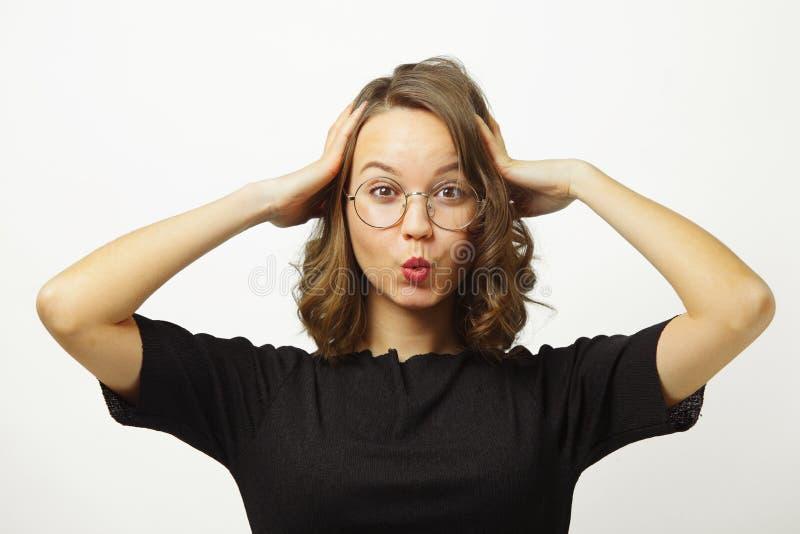 震动的情感妇女投入她的手朝向,拉扯有管、大开眼睛、展示惊奇和震动的嘴唇在白色 库存照片