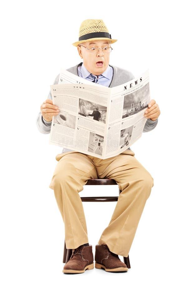 震动的资深绅士在一把木椅子读报纸的 免版税库存图片