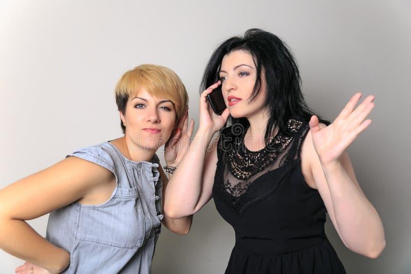 震动窃听的两闲话女孩用对耳朵的手 惊奇的妇女听说坏谣言 间谍活动和隐蔽概念 库存图片