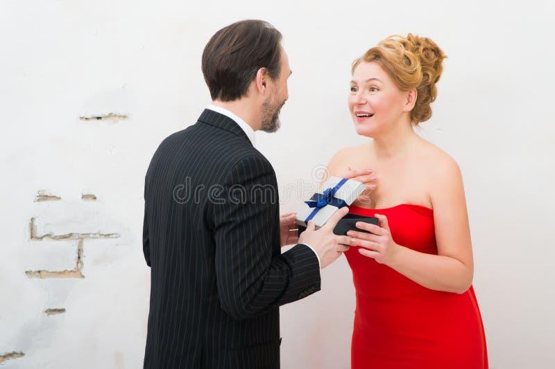 震惊从她的丈夫的美女打开的意想不到的礼物 免版税库存照片