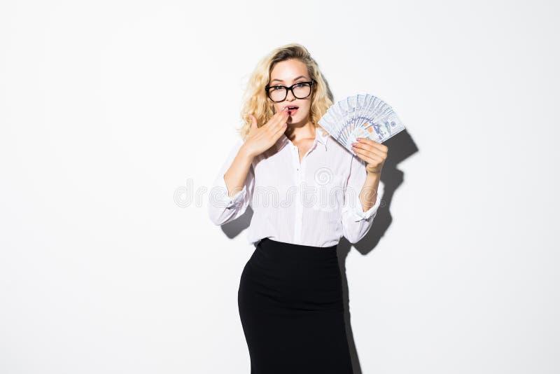 震惊俏丽的女孩藏品束的画象金钱钞票和盖她的嘴被隔绝在白色背景 免版税库存图片