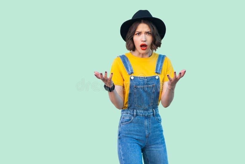 震惊俏丽的年轻行家女孩画象蓝色牛仔布总体、黄色衬衣和黑帽会议身分的与被举的胳膊和 免版税库存图片