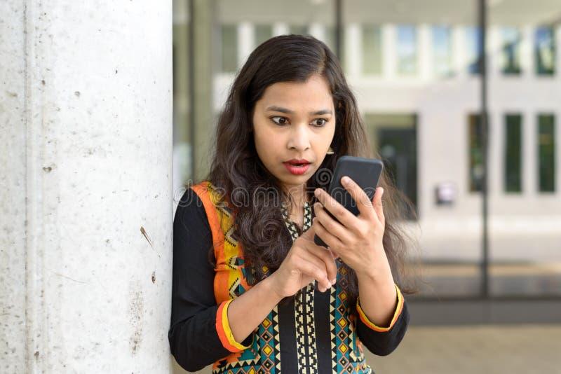 震惊女孩固定的单元电话 免版税图库摄影