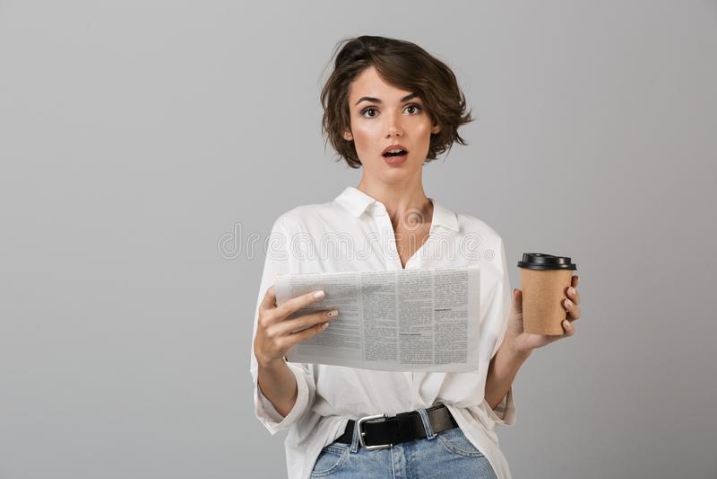 震惊年轻女商人摆在被隔绝在灰色墙壁背景阅读报纸饮用的咖啡 免版税库存图片