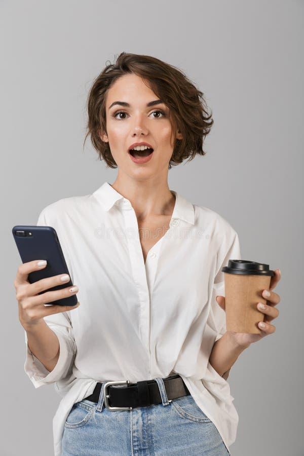 震惊年轻女商人摆在被隔绝在聊天灰色墙壁的背景由手机饮用的咖啡 库存照片