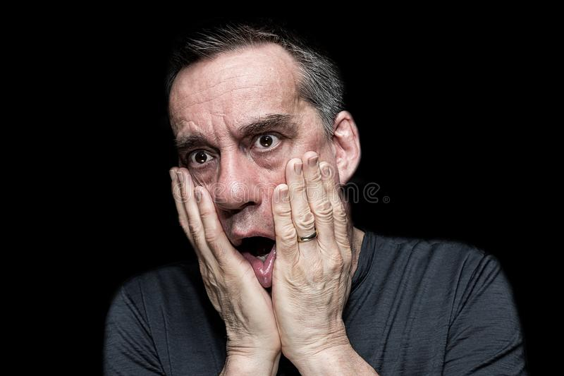 震惊恐惧的人画象用对面孔的手 免版税库存图片