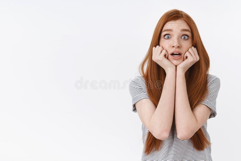 震惊恐慌变了得极度兴奋年轻担心的害怕的红头发人女孩流行的眼睛看起来打颤关心的举行手的jawline 库存照片