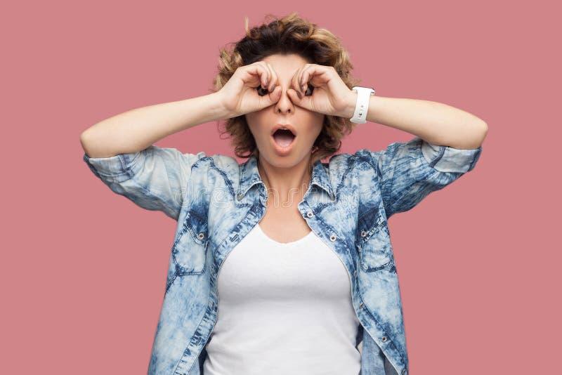 震惊滑稽的年轻女人画象有卷发的在与双筒望远镜的蓝色衬衣身分打手势在眼睛的手和看 免版税库存照片