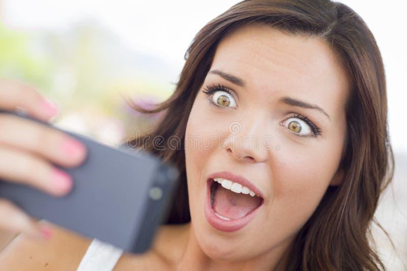 震惊年轻成年女性读书手机Outd 免版税库存照片