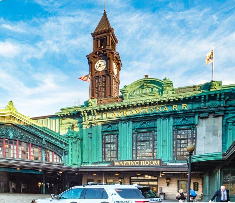 霍博肯,NJ/美国- 2016年6月6日:在霍博肯终端的下班时间 在前景和时钟的通勤者和警车 免版税库存照片