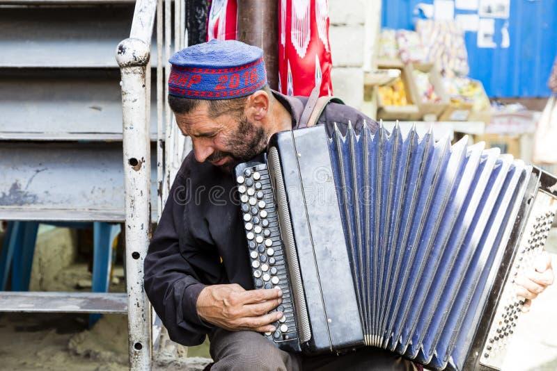 霍罗格,塔吉克斯坦,2018年8月20日:一位老音乐家在义卖市场在霍罗格使用他的手风琴的 免版税库存图片