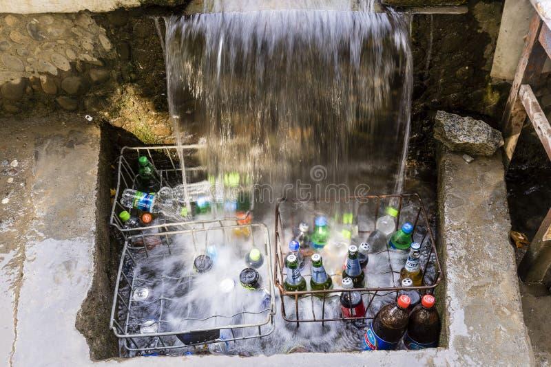 霍罗格,塔吉克斯坦2018年8月25日:在帕米尔高速公路的路旁在塔吉克斯坦饮料冷却在小瀑布下 免版税库存照片