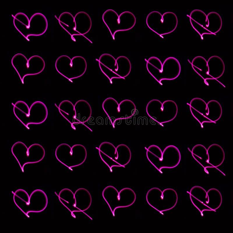 霓虹心脏简单的无缝的背景在黑暗的背景的 库存图片