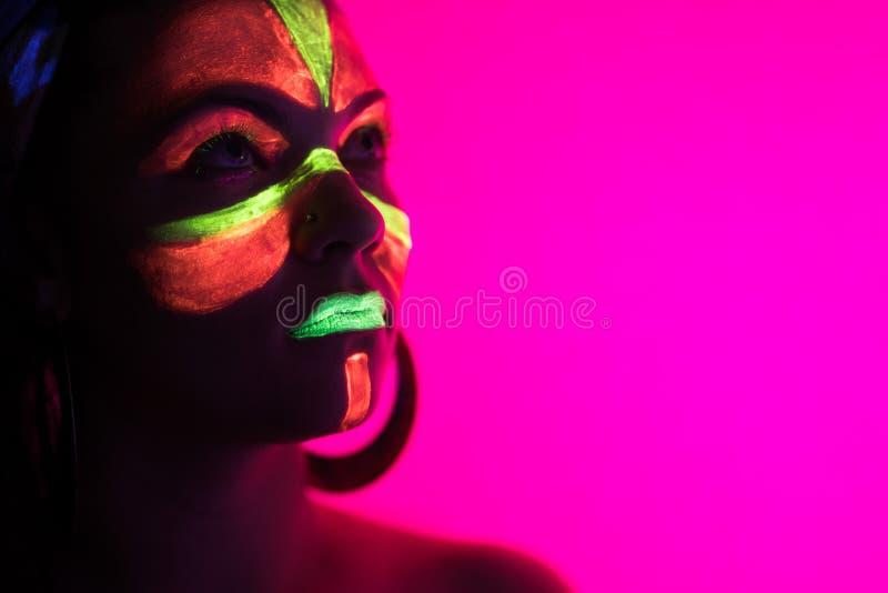 霓虹灯的时尚性感的舞蹈家 发光在紫外光下的萤光构成 夜总会,党,万圣节 库存照片
