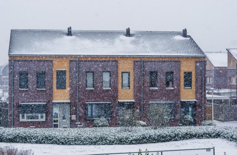 露台的房子在一个冷和多雪的冬日,现代荷兰建筑学,降雪在一个小荷兰村庄 免版税库存照片
