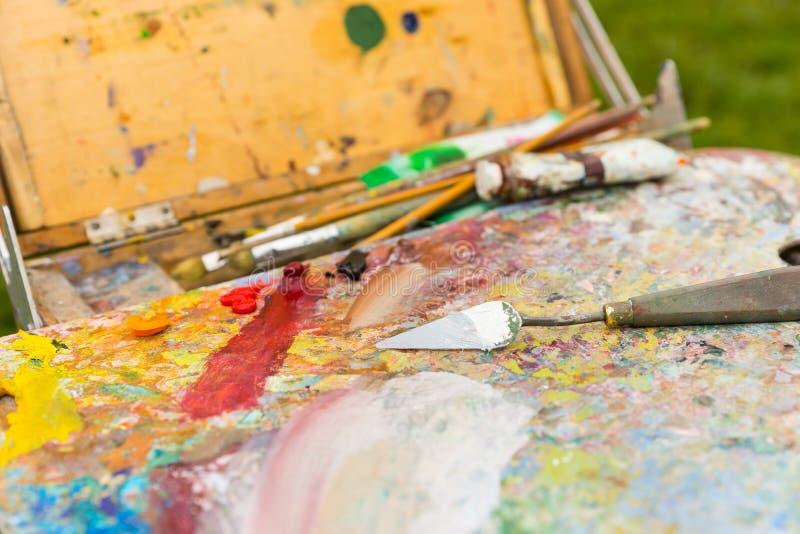 露天关闭在写生簿的画家的工具 免版税库存照片