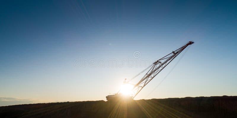 露天开采矿煤矿业的大挖掘机剪影 免版税图库摄影