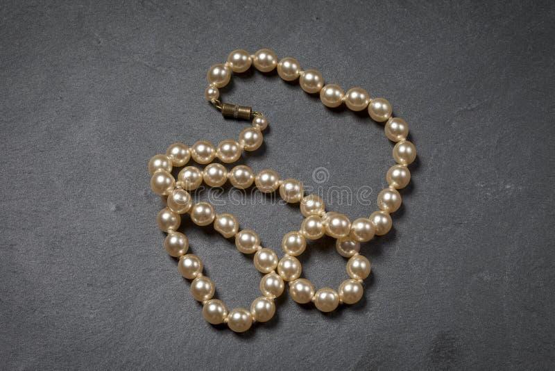露水早晨项链珍珠万维网 珍珠串在黑石背景的 免版税库存图片