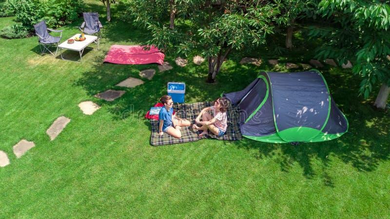 露营地,从上面母亲和女儿空中顶视图有乐趣、帐篷和野营的设备在树,家庭度假下 库存图片
