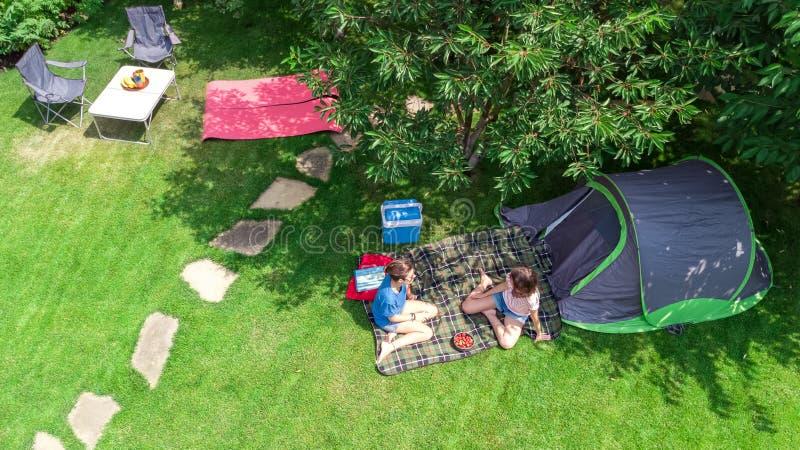 露营地,从上面母亲和女儿空中顶视图有乐趣、帐篷和野营的设备在树,家庭度假下 免版税库存照片