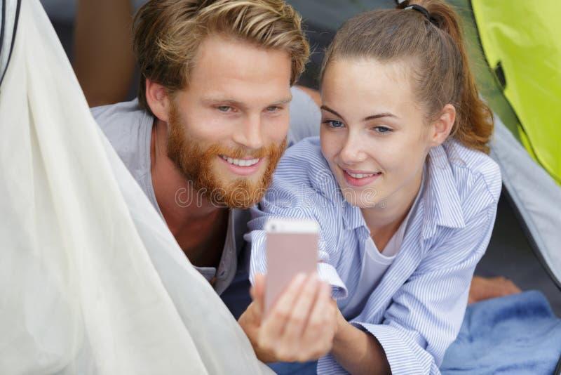 露营期间在帐篷里的快乐年轻夫妇 库存图片
