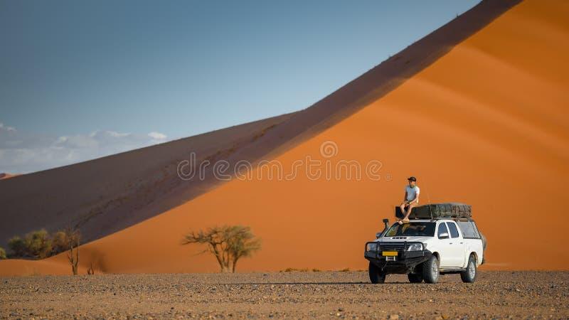 露营车汽车的亚裔游人在沙丘附近 免版税库存图片