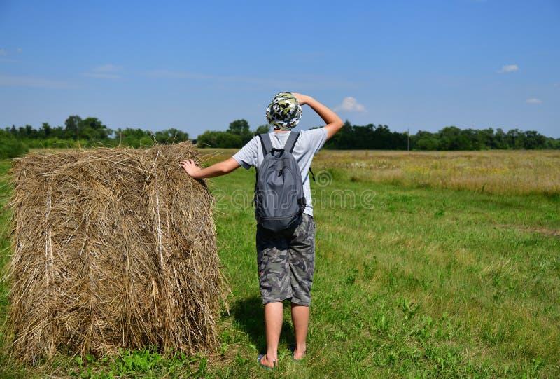 青少年与背包在堆秸杆和朝前看旁边站立 免版税图库摄影