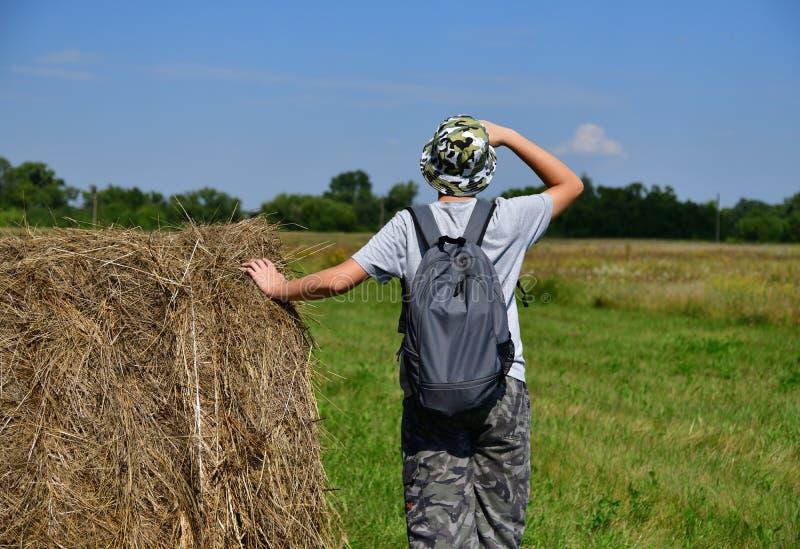 青少年与背包在堆秸杆和朝前看旁边站立 免版税库存图片