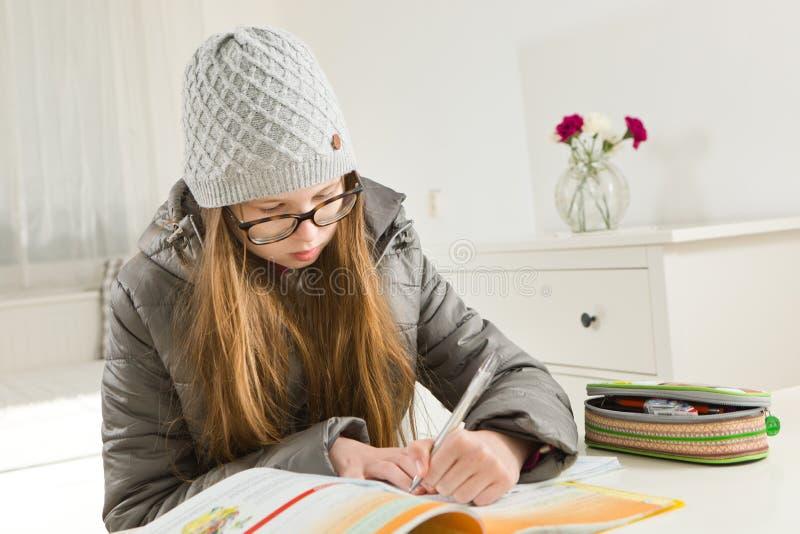 青少年在坚硬情况的女孩去的家庭作业-在冬时,热化不运作 库存图片