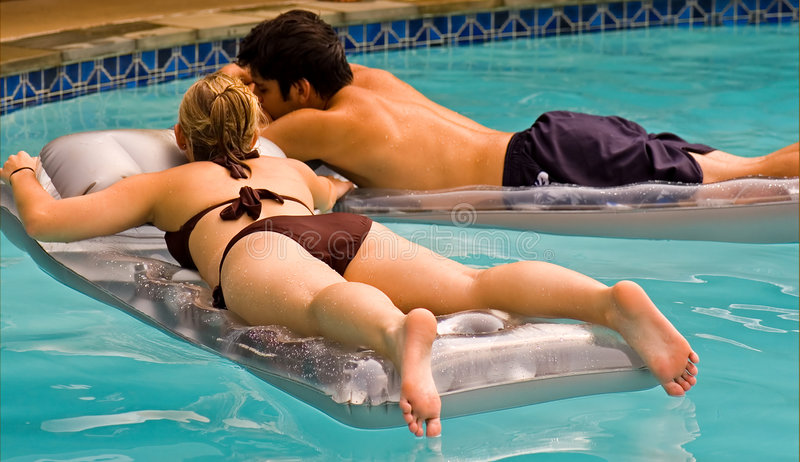 青少年夫妇浮动的池 免版税库存图片
