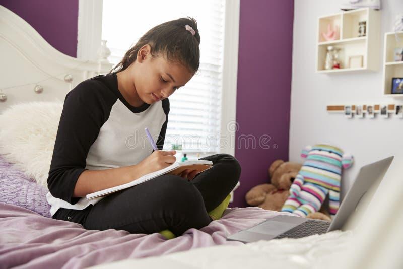 青少年女孩坐她的在笔记本的床文字 库存图片