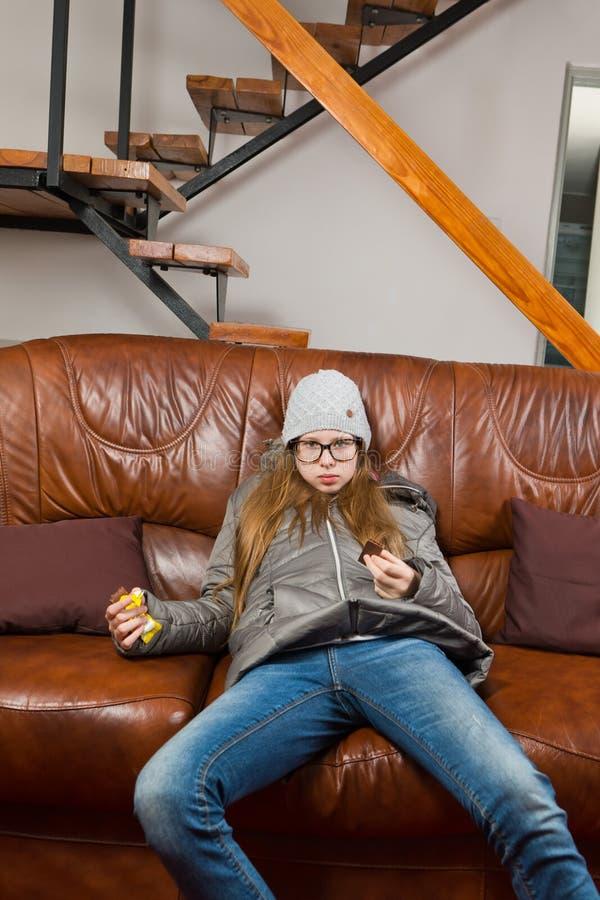 青少年女孩坐沙发和吃巧克力-懒惰做任何东西-早晨是困难的 图库摄影