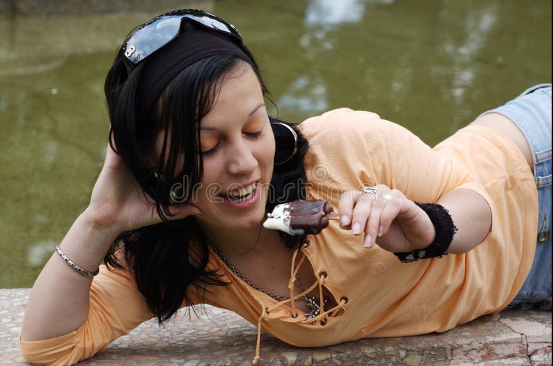 青少年奶油色吃女孩的冰 免版税库存照片