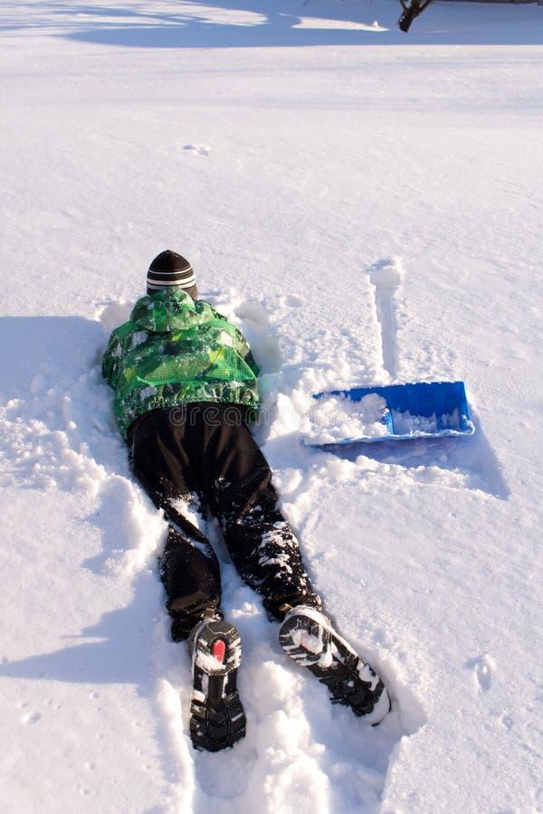 青少年清洗雪铁锹 雪清洁在围场 图库摄影