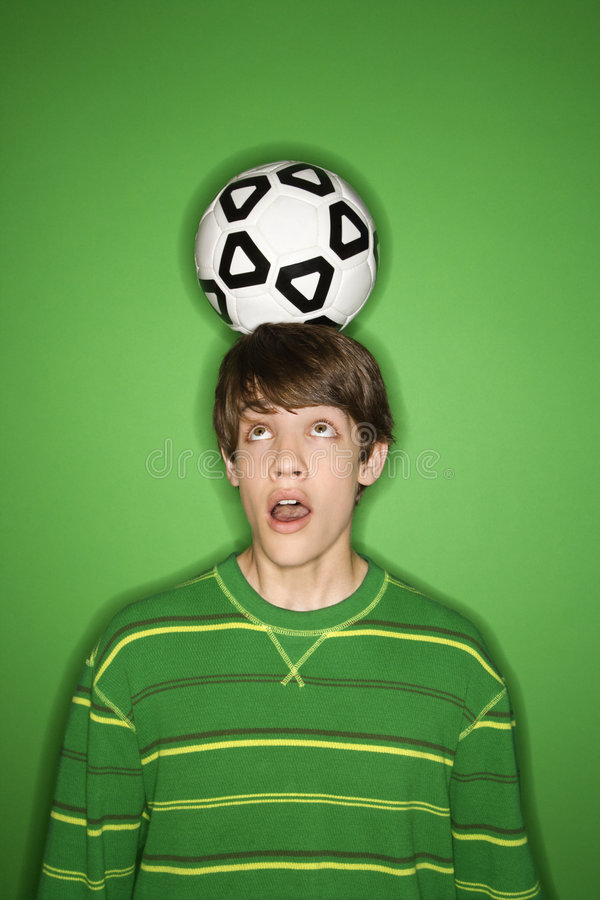 青少年球童白种人顶头的足球 图库摄影
