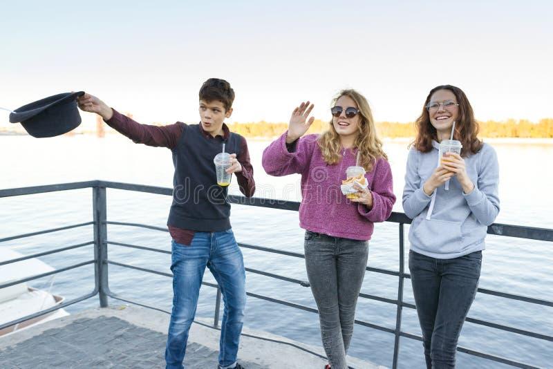 青少年生活方式,男孩和两个青少年的女孩在城市走 笑,吃街道食物的谈的孩子,有 库存照片