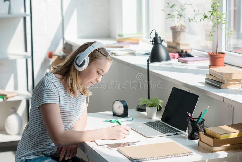 青少年的与耳机的学生女孩听的音乐 免版税库存照片