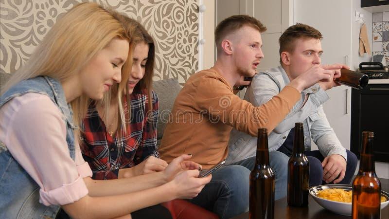 青少年的体育迷在家观看一场foorball比赛并且得到失望对戏剧 免版税库存图片