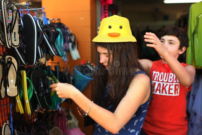 青少年的兄弟和姐妹室外海滩物品的购物 免版税图库摄影