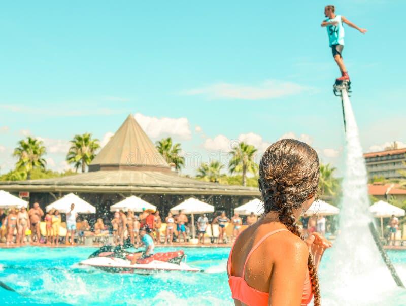 青少年的在水池的女孩观看的飞行板watershow 回到视图 免版税库存图片