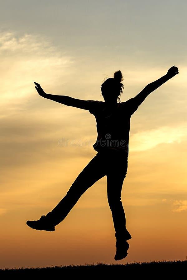 青少年的女孩为喜悦跳在日落 免版税库存图片