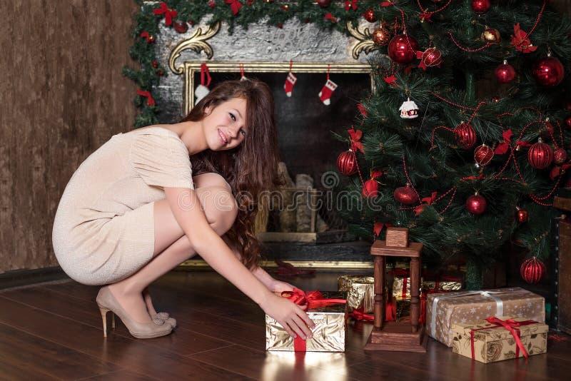 青少年的女孩从圣诞树愉快地微笑的蹲下采取一件新年礼物在圣诞节装饰的壁炉旁边下面 免版税库存照片