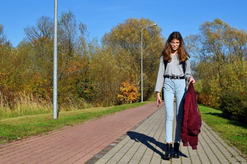 青少年的女孩佩带的玻璃和牛仔裤走的街道 免版税图库摄影