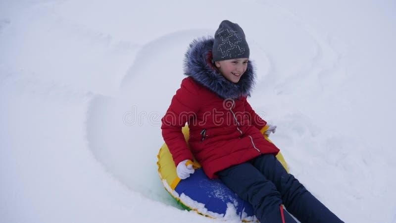 青少年的女孩充当一个冬天公园圣诞节假日 女孩幻灯片在雪的冬天从在雪撬的高小山和  免版税库存图片
